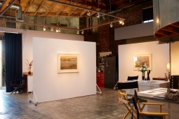 Portable gallery walls break up the space. A number of black director's chairs offer seating at a stationary island/ work space.