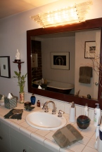 A beautiful art deco style vanity light shines bright above the white tiled sink in the bathroom.