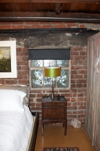 A small vintage nightstand table holds a mid-century modern lamp in front of the metal vine covered window.