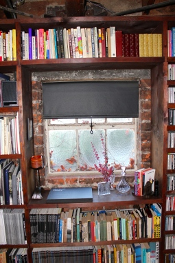 Bookshelf framed windows with simple black pull down shades.